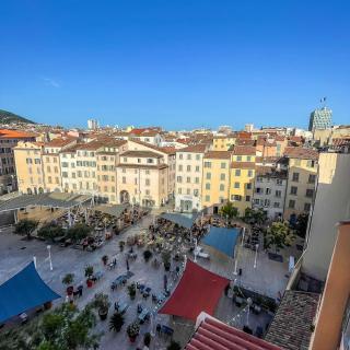 Centre-ville ou centre-village ? 🤔  Elle ressemble, par ses couleurs et façades, à la place d'un petit village de Provence. Pourtant, la Place de l'Équerre se situe bien dans le centre-ville de Toulon !  Restaurants 🥘, bars 🍸 et boutiques de créateurs 👗 font vivre le (nouveau) Quartier des Arts 🎨  🚗 Par l'autoroute ou par la côte (en longeant la mer, c'est quand même plus sympa !), Toulon est située à 30 minutes de l'aéroport.  📸 @levarois_